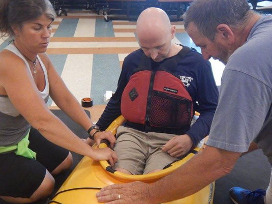 Adaptive Paddler getting into kayak